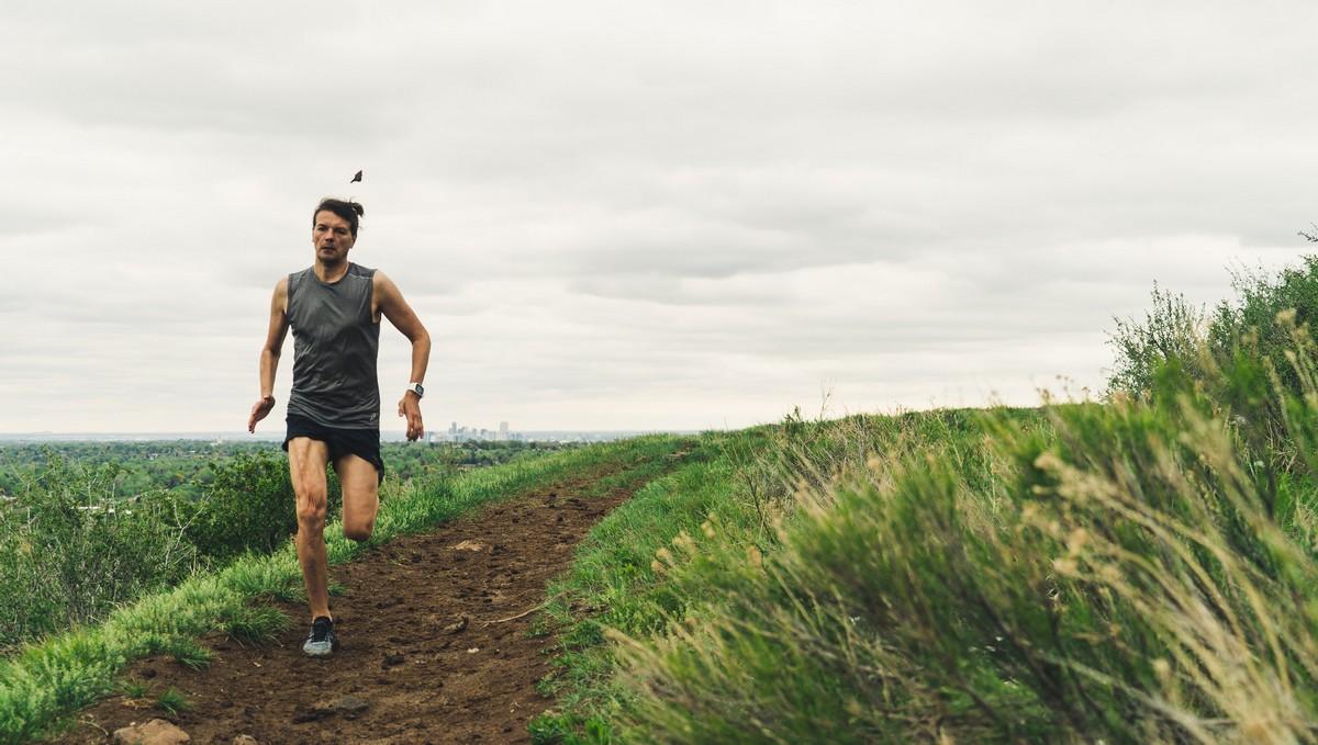 Běžecká výbava, kterou má na sobě mladý běžec v terénu.