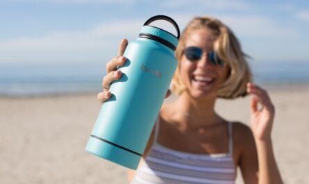 Dívka drží láhev s vodou a dodržuje při sportu pitný režim.