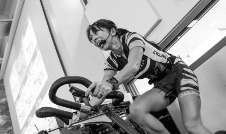 Žena předcvičuje spinning pro návštěvníky fitness centra.